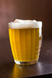 Kubek piwo na drewnianym tle Obraz Stock