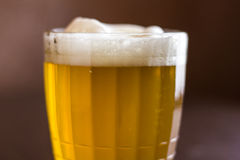 Kubek piwo na drewnianym tle Obrazy Royalty Free