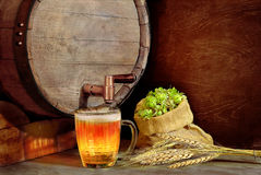 Kubek piwo na tle drewniane baryłki, jęczmień i h, Zdjęcie Stock