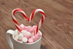 Kubek wypełniał z małymi marshmallowsand cukierku trzcinami Zdjęcia Royalty Free