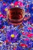 Kubek z czarnej herbaty i błękita kwiatami Fotografia Royalty Free