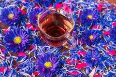 Kubek z czarnej herbaty i błękita kwiatami Obrazy Royalty Free