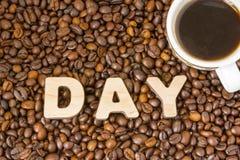 Kubek z sosowaną warzącą kawową pozycją na rozrzuconych piec brown kawowych fasolach obok słowo dnia, zbierającego od ampuły 3D p Zdjęcie Stock