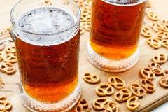 Kubek zimny foamy piwo z niemieckim brezel Zdjęcia Stock