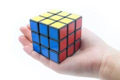 Kuben för Rubik ` s är holden vid handen som isoleras på vit bakgrund Royaltyfri Foto