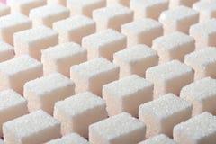 Kuber av förädlat vitt socker den korrekta geometriska formen på en rosa bakgrund Minimalistic abstrakt begreppscreensaver Arkivbild