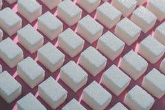 Kuber av förädlat vitt socker den korrekta geometriska formen på en rosa bakgrund Minimalistic abstrakt begreppscreensaver Arkivfoton