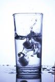 Kuber av naturlig is som plaskar in i exponeringsglas med rent vatten, vert Royaltyfri Foto