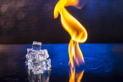 Kuber av is och brand på ett vatten ytbehandlar på en abstrakt backgrou Royaltyfri Foto