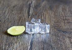 Kuber av is och limefrukt på en trätabell royaltyfria foton