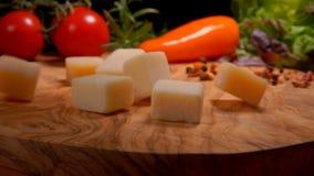 Kuber av parmesanost faller till yttersidan av tabellen stock video