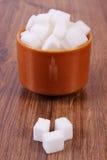 Kuber av socker i den glass bunken på träbakgrund Arkivfoto