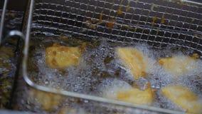 Kuber av tofusmåfiskar i varm olja lager videofilmer
