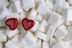 Kuber av vitt socker med bakgrund för två röd hjärtor close upp Top beskådar Arkivfoto