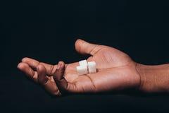 Kuber av vitt socker på svart man gömma i handflatan, closeupen royaltyfria bilder