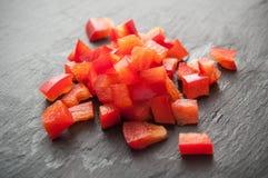 Kuber för röda peppar på svart tavlabakgrund Arkivbilder