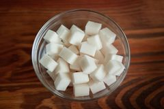 Kuber för vitt socker i den glass bunken på trätabellen Arkivbild
