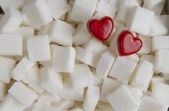 Kuber för vitt socker med bakgrund för två röd hjärtor close upp Top beskådar Royaltyfria Foton