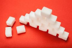 Kuber f?r vitt socker p? r?d bakgrund fotografering för bildbyråer