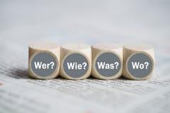 Kuber med orden som, hur, vad, var i tysk Arkivfoto