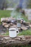 Kubków stojaki na beli blisko ogienia przy campsite Obraz Royalty Free