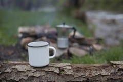 Kubków stojaki na beli blisko ogienia przy campsite Fotografia Stock