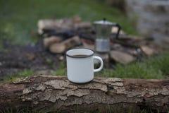 Kubków stojaki na beli blisko ogienia przy campsite Fotografia Royalty Free