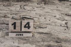 Kubkalender för juni på träbakgrund Arkivbild