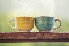 Kubki z gorącym napojem z herbatą na drewnianym stojaku outdoors zdjęcie stock