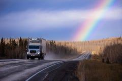Kublastbil på vägen i det regnbågeYukon landskapet royaltyfri foto