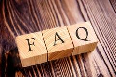 Kubussen met een inschrijving FAQ op de oude raad stock foto