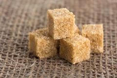 Kubussen van bruine suiker op jutezakken Stock Foto