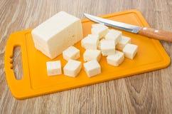 Kubussen van feta-kaas op plastic scherpe raad, keukenmes Royalty-vrije Stock Foto's