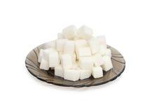 Kubussen van suiker op de zwarte plaat Stock Afbeelding