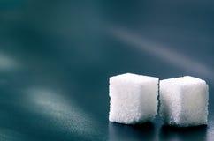 Kubussen van suiker op een donkere achtergrond Ongezonde ingrediënten De suiker van het stuk Stock Afbeeldingen