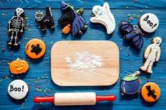 Kucbarscy Halloween piernikowi ciastka w kształcie kościec, mamusia Cukierki zbliżają biurko i toczną szpilki błękitny tło wierzc fotografia stock