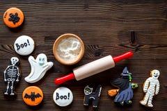 Kucbarscy Halloween piernikowi ciastka w kształcie kościec, mamusia Cukierki zbliżają biurko i toczną szpilki Drewniany tło wierz zdjęcia stock