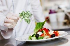 Kucbarska szef kuchni ręka dekoruje przygotowanego sałatkowego jedzenie obraz royalty free