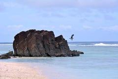Kucbarska wyspiarka skacze od Tuoro czerni skały w Rarotonga gruchu zdjęcia stock