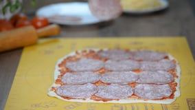 Kucbarski kładzenie salami nad mozzarellą na surowym pizzy zakończeniu zbiory