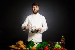 Kucbarski szef kuchni z warzywa splah i czarnym ciemnym tłem Karmowa muzykalna harmonia Szef kuchni żongluje z warzywami i innym  Zdjęcia Stock