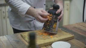 Kucharz naciera marchewki na grater zbiory