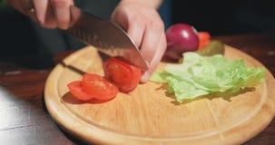 Kucharz pokraja? pomidoru ostrym no?em na drewnianej desce Robi? jarzynowa sa?atka, jarski posi?ek, ?wiezi pomidory zdjęcie wideo