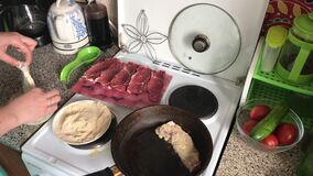 Kucharz zamacza kawałki mięso w ciasto naleśnikowe w breadcrumbs, wtedy Blisko smaży niecki pierwszy porcja mięso smaży zbiory wideo