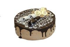 Kuchen bedeckt mit Schokolade und mit weißen Rosen verziert stockfotografie