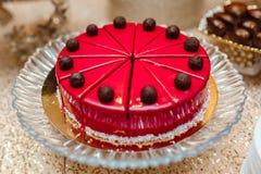 Kuchen in der roten Glasur auf Tabelle, Schnitt in Stücke verziert mit Schokoladenbällen Schokoriegel lizenzfreie stockbilder