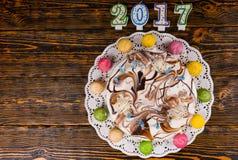 Kuchen des neuen Jahres mit vielen Kerzen und macarons als Uhr nahe Lizenzfreie Stockfotos