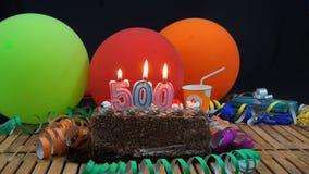 Kuchen des Schokoladengeburtstages 500 mit den Kerzen, die auf rustikalem Holztisch mit Hintergrund von bunten Ballonen brennen stockbild