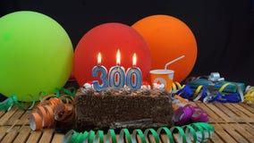 Kuchen des Schokoladengeburtstages 300 mit den Kerzen, die auf rustikalem Holztisch mit Hintergrund von bunten Ballonen brennen stockbilder