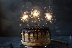 Kuchen des strengen Vegetariers Blaubeerverziert mit dem Schokoladenbereifen, -beeren und -Wunderkerze auf dunklem Steinhintergru Stockbild